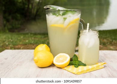 Pitcher of lemonade and glass on a yellow napkin with lemons outside by a lake in summer