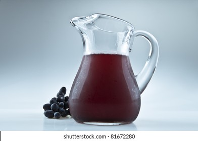 A pitcher of lemonade and some grapes