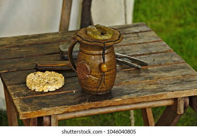 Pitcher made of wood and several other objects resting on a wooden table.