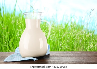 Pitcher of milk on wooden table against grass background