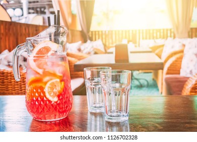 Pitcher with orange juice and two empty mugs stand on a table in a cafe on a hot, sunny day. Copy space for text.