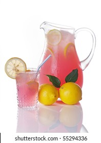 Pitcher of pink lemonade with glass and whole lemons