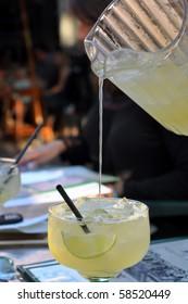 Pitcher pouring liquid into margarita glass.