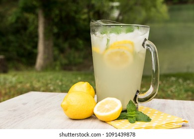 A pitcher of tasty lemonade outside on a hot summer day