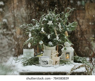 A pitcher of white metal with fir branches decorated with Christmas toys white and chickadee in the snow garden