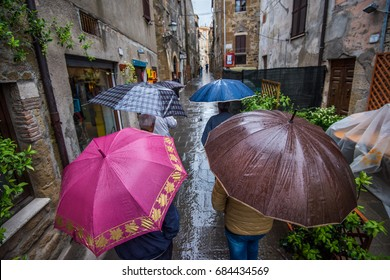 Pitigliano, Italy - May, 2015: Group of people walking around the city under umbrellas