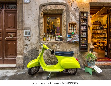 Pitigliano, Italy - May, 2015: Lime color Vespa scooter on the streets of Pitigliano