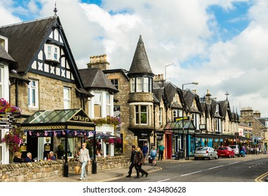 Pitlochry, Scotland - September 17, 2014: the main street in Pitlochry on a sunny day. People roams the street as the town prepares for the nearby 2014 Gleneagles Ryder Cup of golf.