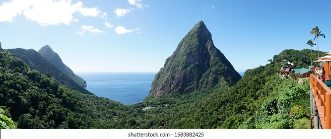The Piton mountains Gros Piton and Petit Piton in a lush green forest next to the blue ocean on Saint Lucia Island in the Caribbean Sea.