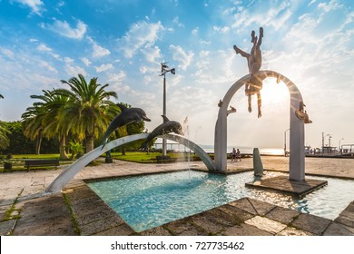"""PITSUNDA, ABKHAZIA, SEPTEMBER 23, 2017: Famous sculptural composition """"The Sea"""", which depicts pearl divers and dolphins, in  Pitsunda in the rays of the rising sun in the central beach."""