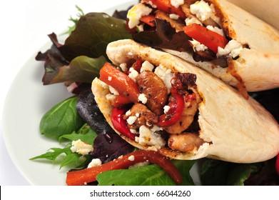 Pitta bread on salad leaves filled with a chicken, vegetables and feta cheese