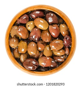 Pitted Taggiasca olives in wooden bowl. Small, fruity olives from Taggia in Linguria, a region in Italy. Preserved in olive oil, used as table olives. Macro food photo closeup from above over white.