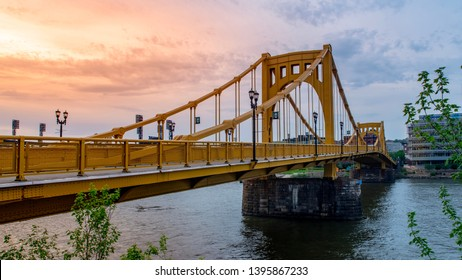 Pittsburgh, PA—May 1, 2019; sunset on cloudy evening with steel yellow Andy Warhol bridge crossing the Allegheny river downtown in the foreground