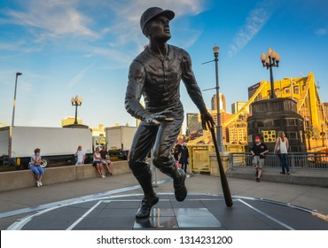 Pittsburgh, PA / USA - 08-28-2014: Statue of famous baseball player Roberto Clemente at Pittsburgh Pirates' PNC Park arena in front of yellow bridge named after him.