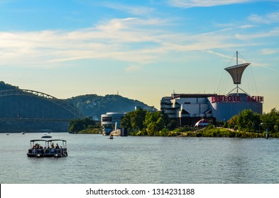 Pittsburgh, PA / USA - 08-28-2014: View of Ohio River with bridge and the Carnegie Science Center museum at center, with a party boat in the foreground, as seen from Point State Park.