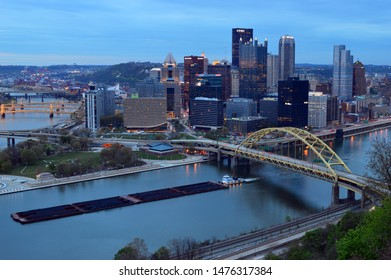 Pittsburgh, PA, USA May 5, 2014 A coal barge plies the Allegheny River, passing the skyline of Pittsburgh, Pennsylvania