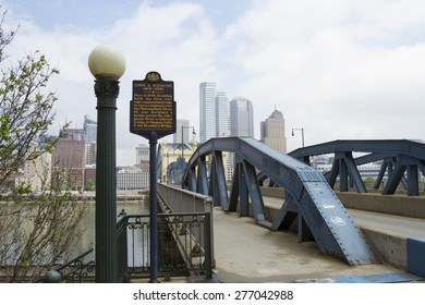 Pittsburgh, PA, USA - May 5, 2015 : Smithfield street bridge with marker memorializing designer John A. Roebling with Pittsburgh city skyline.