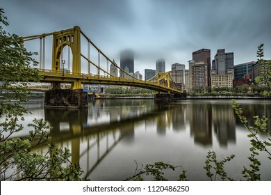 Pittsburgh, Pennsylvania - May 13, 2018 : Reflections of the Pittsburgh skyline and the Andy Warhol Bridge in the Allegheny River on a cloudy, foggy day.