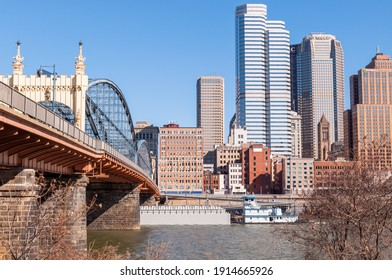 Pittsburgh, Pennsylvania, USA 2-6-21 A tugboat and barge travel on the Monongahela river going under the Stanwix street bridge  with downtown Pittsburgh in the background on a sunny winter day