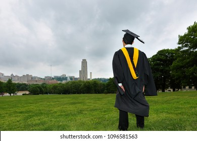 Pittsburgh, Pennsylvania USA - May 20, 2018: A Carnegie Mellon Graduate wearing graduation gown Looking the campus at Flagstaff Field. Carnegie Mellon University is ranked top 25 Universities in USA.