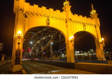 Pittsburgh, Pennsylvania / USA - November 7, 2018: Arches of the Smithfield Street Bridge are lit with warm streetlights at nighttime over the Monongahela River.