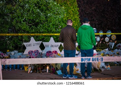 Pittsburgh, Pennsylvania / USA – Oct 30 2018: Passers by pay their respects to the victims of Saturdays shooting at the memorial outside of the Tree of Life synagogue in Pittsburgh.