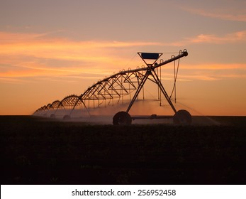 Pivot water system on a farm field at sunset, agriculture irrigation machine silhouette