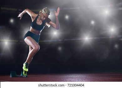 pixelated design of woman  sprinter leaving starting blocks on the athletic  track in front of big modern stadium with lights and flares. Side view. exploding start