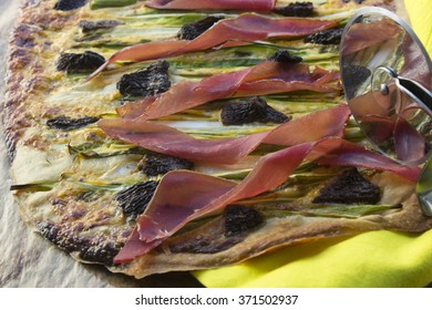 pizza with aspargus and morel on a cutting board and knife