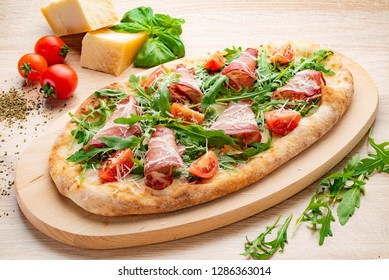 pizza with bacon and cherry tomatoes on the wood board