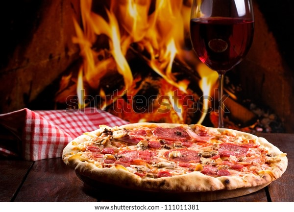 pizza with bacon, salami and glass of wine