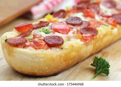 Pizza Baguette with salami on wooden board