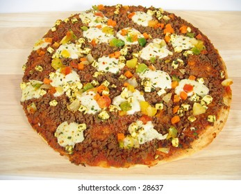A pizza with beef, cheese and paprika.