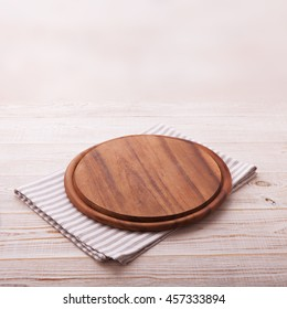 Pizza board with a napkin on white wooden table. Top view mock up square
