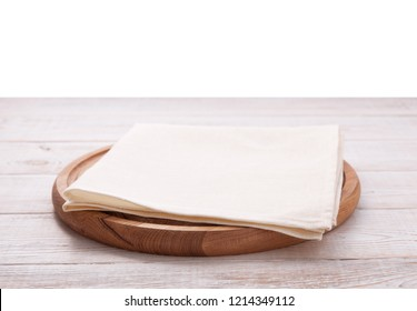 Pizza board with a napkin on wooden table isolated on white. Top view mock up