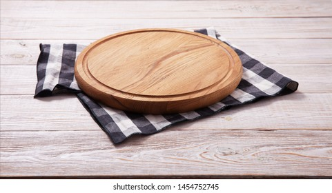 Pizza board, with tablecloth on wooden table and summer sea background. Top view mockup