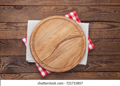 Pizza board and tablecloth on wooden table. Top view mock up