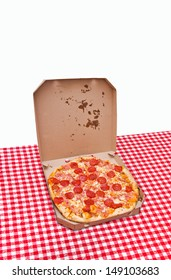 Pizza in a box. Tasty pizza with pepperoni sausage in white cardboard box on kitchen table