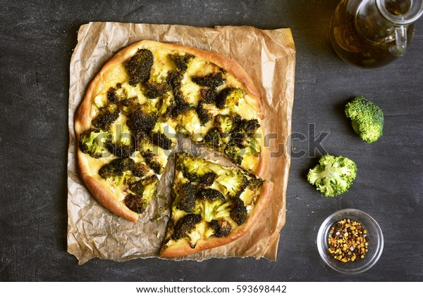 Pizza with broccoli and cheese on dark background, top view
