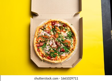 Pizza in a cardboard box. Space for text. View from above. Pizza delivery. Pizza menu.