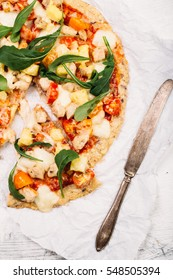 Pizza with cauliflower base, chicken, ruccola leaves, cherry tomatoes and mozzarella cheese on white background Top view