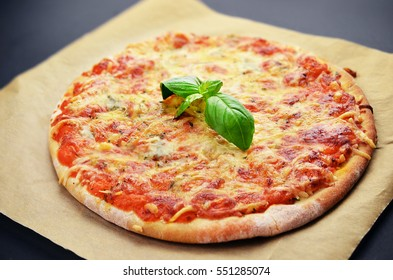 Pizza with cheeses and basil on black table