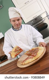 Pizza chef holding slice of pizza and smiling at you