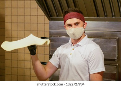 a pizza chef in a mask makes pizza dough, tosses it