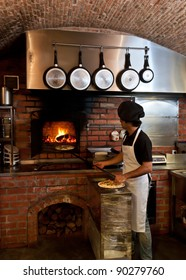 Pizza Chef puts the pizza inside the Wood Oven to bake