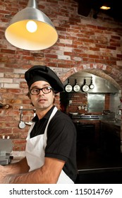Pizza Chef is standing at the kitchen in a pizza restaurant working making dough while listening to customers orders