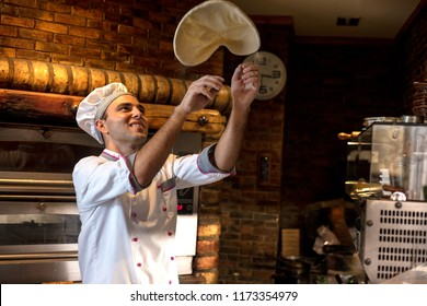 Pizza chef tossing pizza dough in the air