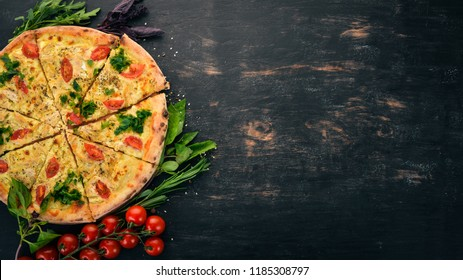 Pizza with cherry tomatoes, suluguni cheese and basil. Italian cuisine. On a wooden background. Free space for text. Top view.