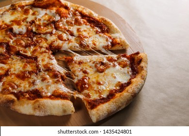 Pizza with chicken cheese and pepperoni, a piece of which is cut and laid out like a pakman, is on a wooden board and a brown background. Cheese spreads flowing streaks