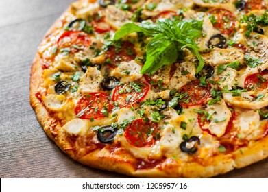 Pizza with Chicken meat, Mozzarella cheese, tomato, olive. Italian pizza on wooden background